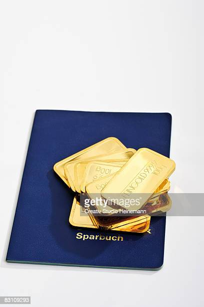 Gold bars on bank book against white background, high angle view