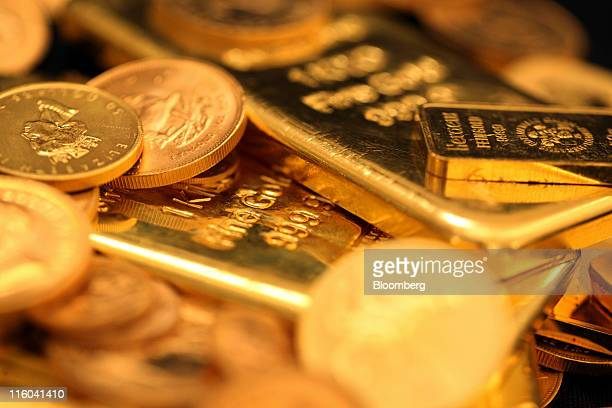Gold bars and coins are seen in this arranged photograph at Gold Investments Ltd bullion dealers in London UK on Tuesday June 14 2011 day June 14...