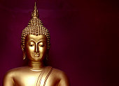 gold bhuddha statue close up smile face on vintage dark red background low key style