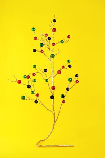 Gold branch with glittery ornaments on yellow background. - gettyimageskorea