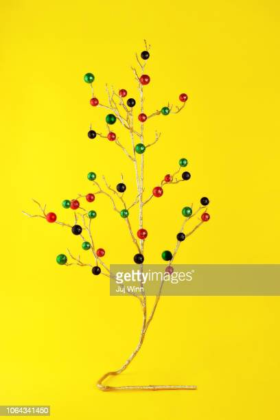 Gold branch with glittery ornaments on yellow background.
