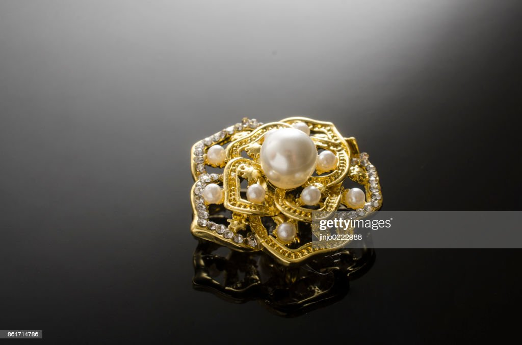 c62cca7a36f72 Gold Brooch Flower With Pearl Isolated On Black Stock Photo - Getty ...