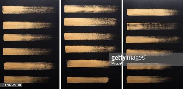 gold brush stroke painting on black paper - elemento de desenho - fotografias e filmes do acervo