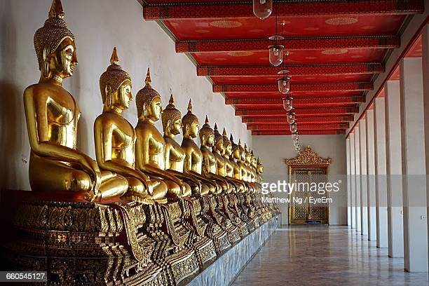 gold buddha statues in row at wat pho corridor - wat pho stock pictures, royalty-free photos & images