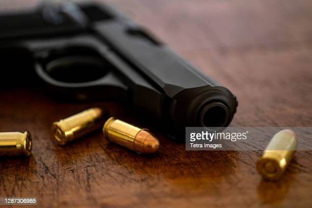gold bullets and pistol on wooden surface - medium group of objects stock pictures, royalty-free photos & images
