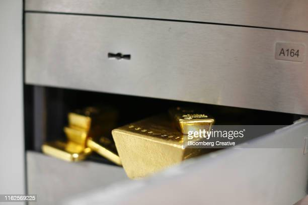 gold bullion bars sit in a safety deposit box - safety deposit box stock pictures, royalty-free photos & images