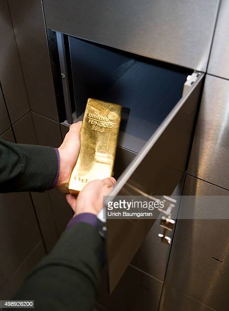 Gold bullion in the strong room of pro aurum Goldhouse in Munich Hand puts a 125 kg gold bullion in a deposit box