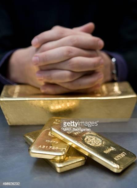 Gold bullions in the strong room of pro aurum goldhouse in MunichHands with 1 kg and 125 kg gold bullions Hände mit 1 kg und 125 kg Goldbarren