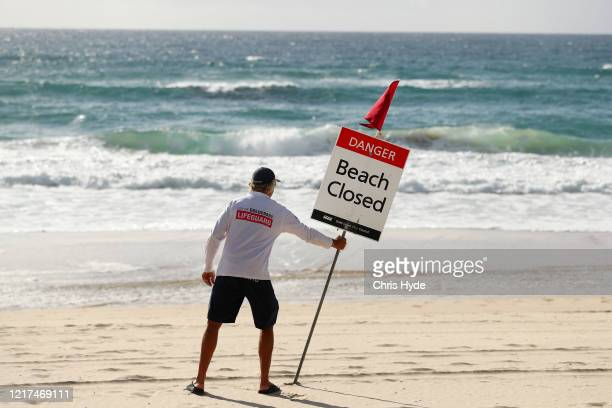 Gold Coast Lifeguard erects a Beach Closed sign at Surfers Paradise beach on April 08, 2020 in Gold Coast, Australia. A number of major Gold Coast...
