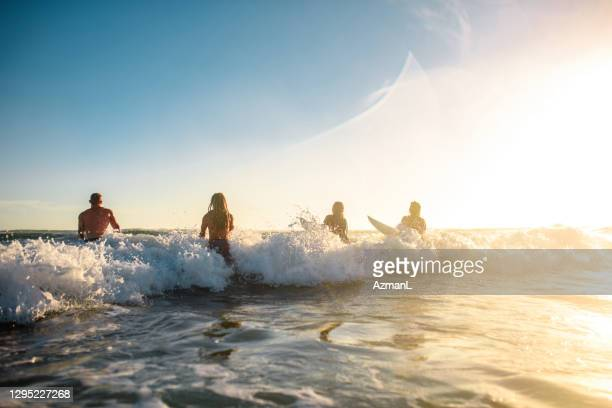 gold coast surfers running into mist and waves at sunrise - coral sea stock pictures, royalty-free photos & images