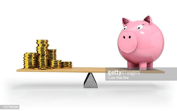 Gold coins and Piggy Bank balancing on a see saw
