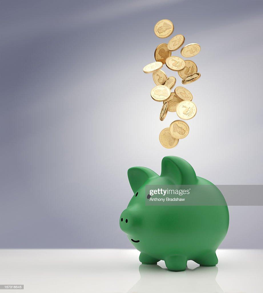 Gold coins falling into a green piggy bank : Foto de stock