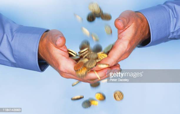 gold coins falling through business man's hands - gier stock-fotos und bilder