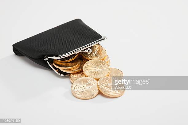 Gold coins spilling out of change purse