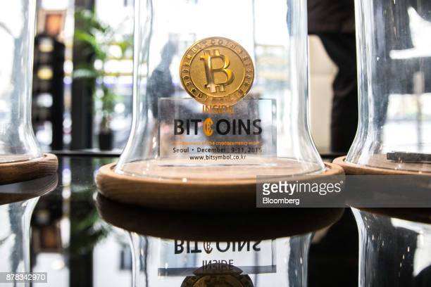 A gold colored bitcoin token sits on display under a glass cloche inside the offices of La Maison du Bitcoin bank in Paris France on Thursday Nov 23...