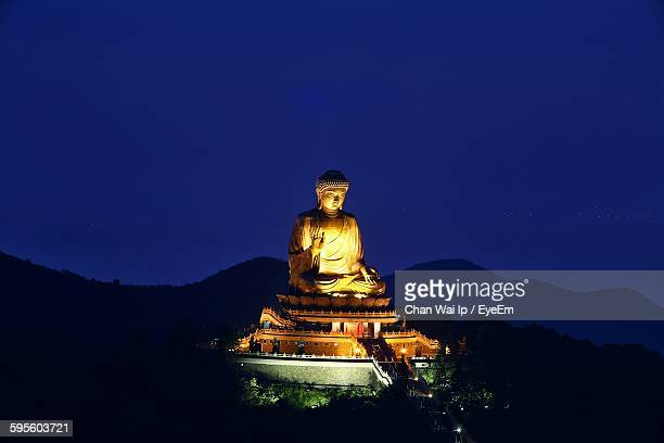 Gold Colored Buddha Statue At Po Lin Monastery Against Clear Sky