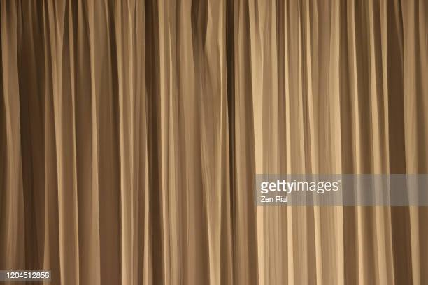 gold colored curtain hanging and creating vertical linear patterns - sheer fabric stock pictures, royalty-free photos & images
