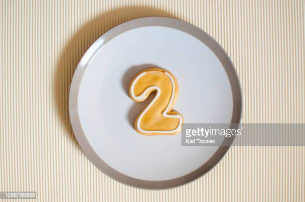 gold colored number 2 cookie on a white plate - number 2 stock pictures, royalty-free photos & images