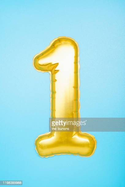 gold colored number one on blue background - anniversary stock pictures, royalty-free photos & images