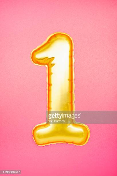 gold colored number one on pink background - première photos et images de collection