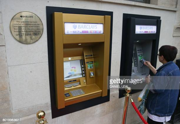 A gold coloured automated teller machine is pictured outside a branch of British bank Barclays in Enfield north London on June 27 on he 50th...