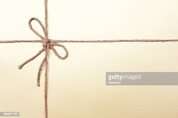 gold coloured packaging with knotted string - string stock pictures, royalty-free photos & images