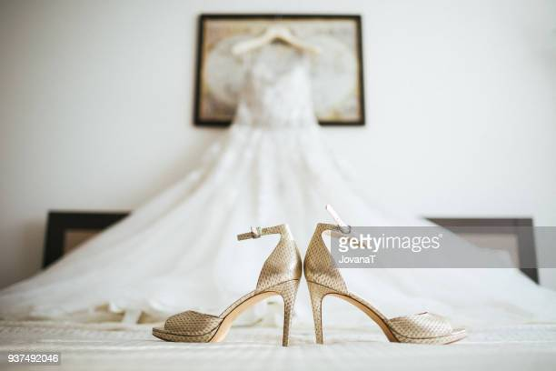 gold coloured wedding high heels on white sheet - gold shoe stock photos and pictures
