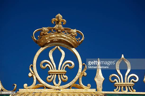gold crown and fleur-de-lis on the grand trianon gates against a blue sky in the gardens of the palace of versailles, paris, france - corona de oro foto e immagini stock