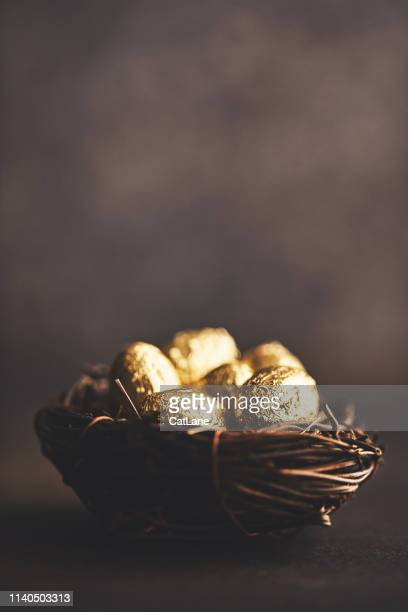 gold eggs in nest. easter background - easter egg stock pictures, royalty-free photos & images