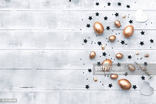 Gold eggs with black decorations over wooden background