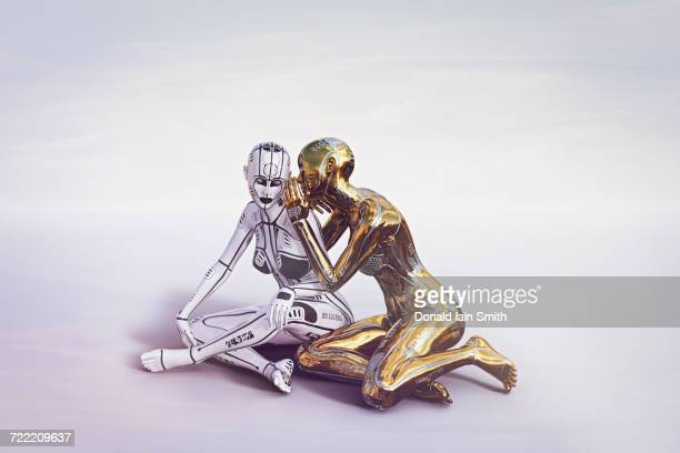 Gold female cyborg sitting and whispering to white cyborg