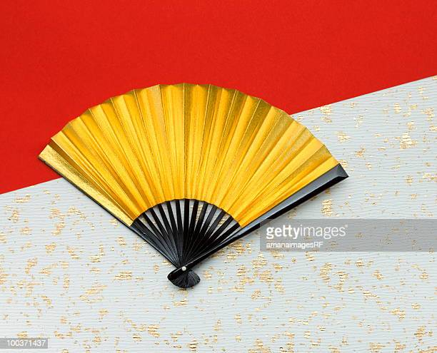 gold folding fan on japanese paper - hand fan stock pictures, royalty-free photos & images