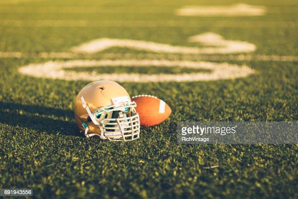 gold football helmet on field - sports event stock pictures, royalty-free photos & images
