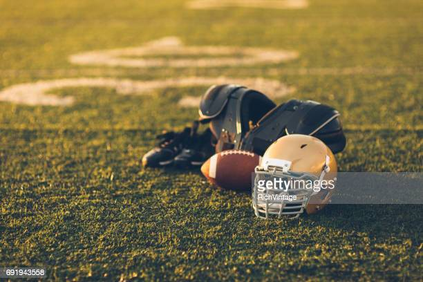 gold football helmet on field - american football strip stock pictures, royalty-free photos & images