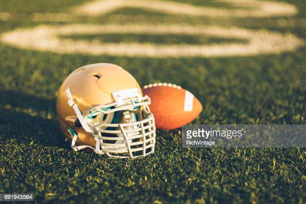 gold football helmet on field - notre dame football stock photos and pictures