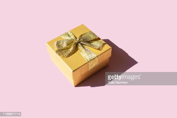gold gift box  on pink background - geschenk stock-fotos und bilder