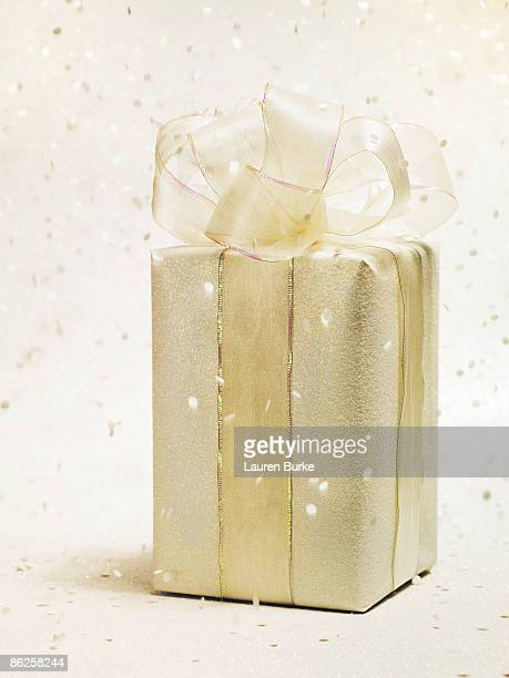Gold Gift on Glitter Background with Confetti