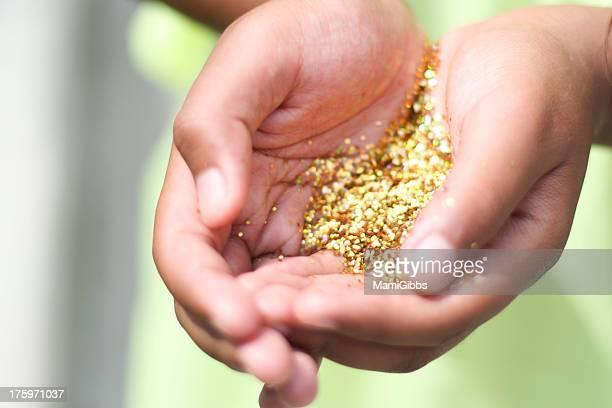 Gold glitter  in girl's hands