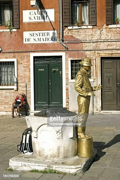 A gold golden mime performs near Academia elderly woman naps sleeps Venice Italy