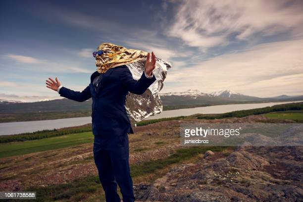 gold headed businessman escaping from work. head full of ideas metaphor - metallic suit stock photos and pictures