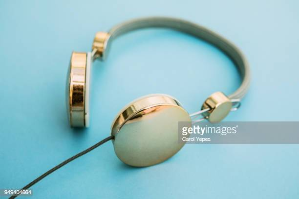 gold headphones in blue background