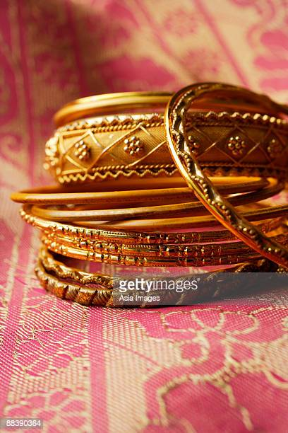 gold Indian bangles on pink sari cloth
