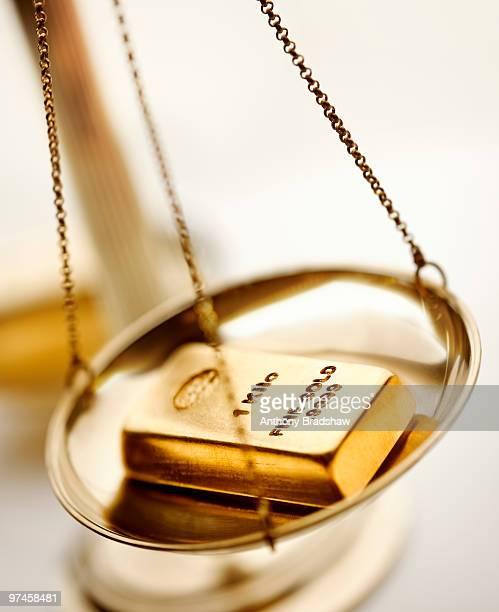 Gold ingot balancing on scales