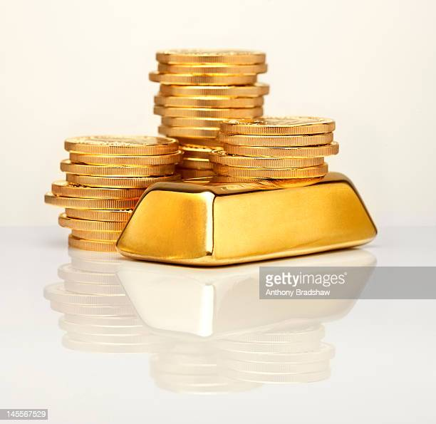 Gold ingot in front of gold coins