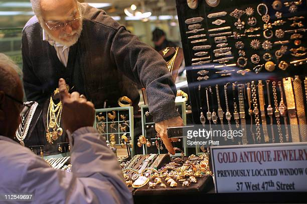 A gold jeweler reaches for a display piece in the window on April 19 2011 in New York City Gold futures climbed to a record $1500 level today...