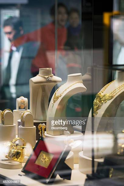 Gold jewelry sits on display as a pedestrian is reflected in the window of a Chow Tai Fook Jewellery Group Ltd store in the shopping district of Tsim...