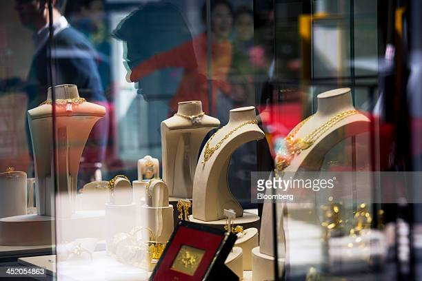 Gold jewelry sits on display as pedestrians are reflected in the window of a Chow Tai Fook Jewellery Group Ltd store in the shopping district of Tsim...