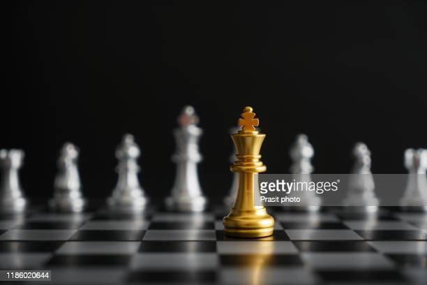 gold king in chess game face with the another silver team on black background. concept for company strategy, business victory or decision - tabuleiro de xadrez imagens e fotografias de stock