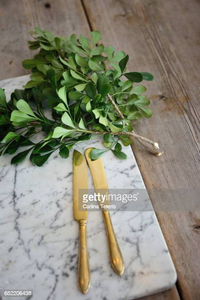 gold knives on a marble cutting board on wood table