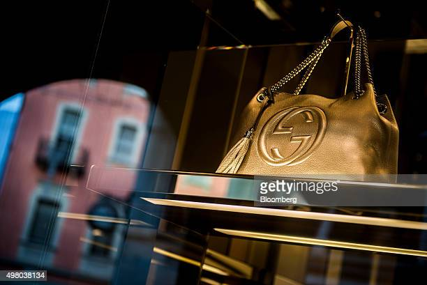 A gold leather handbag sits in the window display of a Gucci luxury goods store operated by Kering SA in Lugano Switzerland on Thursday Nov 19 2015...